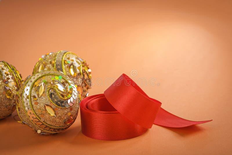 Goldener Weihnachtsflitter und rotes Band auf braunem Hintergrund lizenzfreies stockfoto