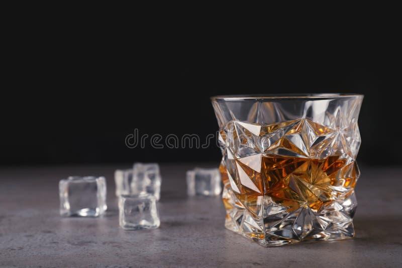 Goldener Whisky im Glas mit Eiswürfeln auf Tabelle lizenzfreie stockbilder