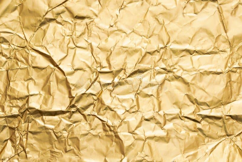Goldener zerknitterter abstrakter Hintergrund der Folienpapier-Beschaffenheit lizenzfreies stockbild