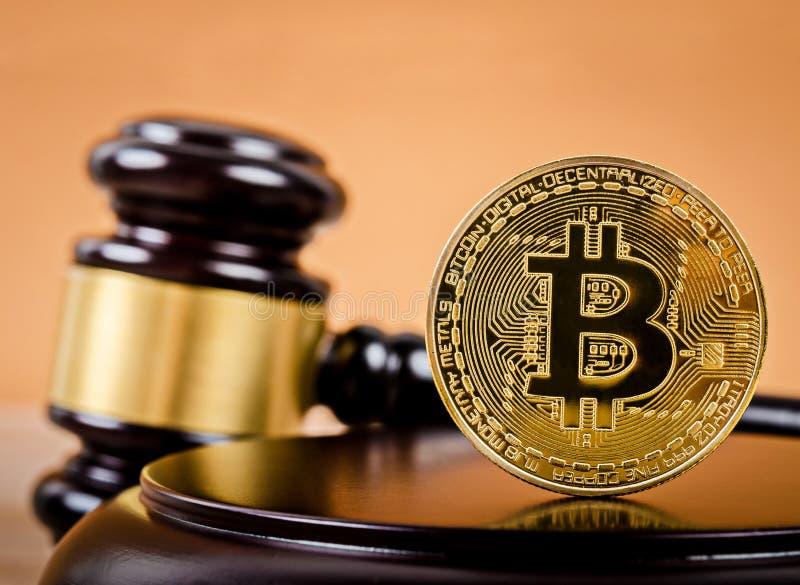 Goldenes bitcoin auf hölzernem Sockel des Richterhammers stockfotos