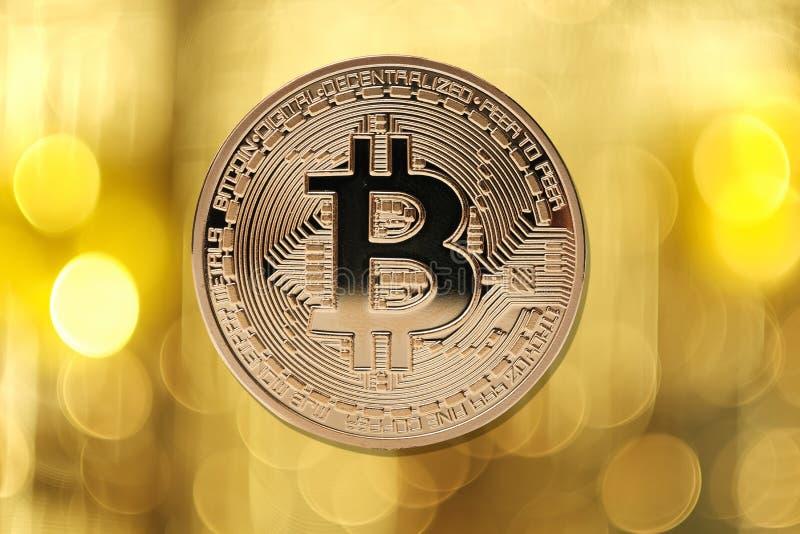 Goldenes bitcoin auf unscharfem hellem Hintergrund lizenzfreie stockfotos