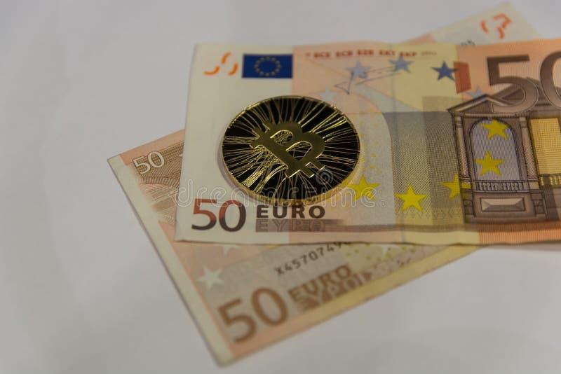Goldenes bitcoin auf zwei fünfzig Eurorechnungen lizenzfreies stockfoto
