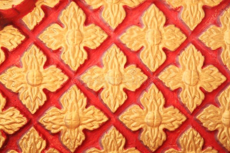 Goldenes Blumenmuster auf roter Wand lizenzfreies stockfoto