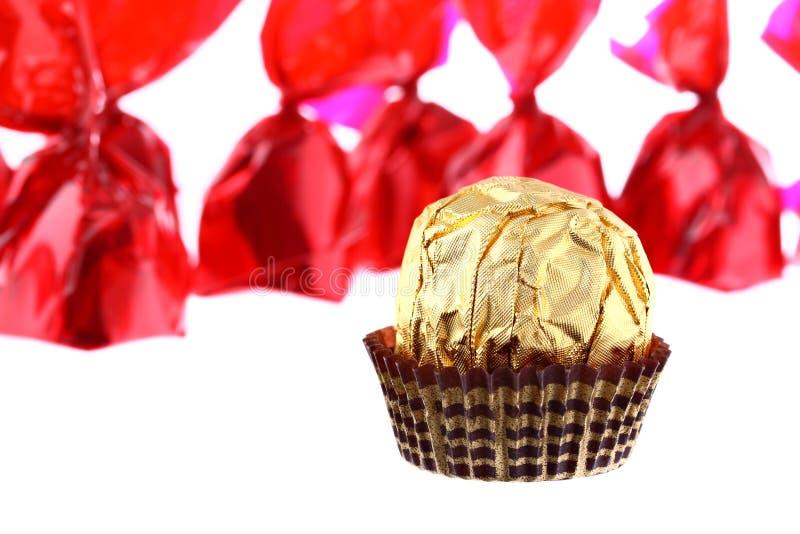 Goldenes Bonbon vor den roten Bonbons getrennt stockfotografie
