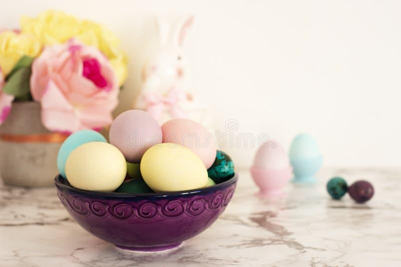 Goldenes Ei über grünem Steigungshintergrund Purpurrote Schüssel mit bunten Eiern in den Mattfarben Heller Marmorhintergrund stockfotos