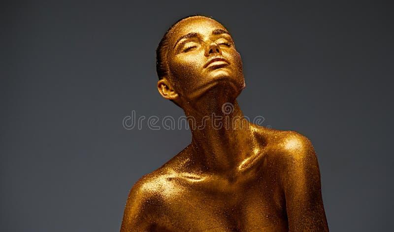 Goldenes Hautschönheits-Frauenporträt Modemädchen mit goldenem Make-up des Feiertags Körper Art lizenzfreie stockfotos