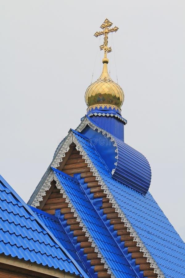 Goldenes Kreuz einer Dorfkirche lizenzfreie stockbilder