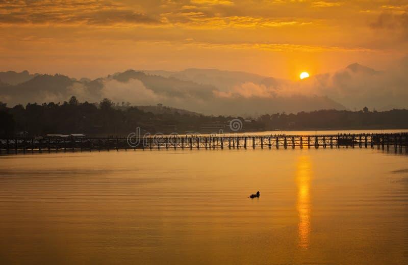 Goldenes Morgenlicht Montag-Brücke ist die lange Holzbrücke Offizieller Name ist Attanusorn-Brücke Ist der Weg der Dorfbewohner lizenzfreies stockfoto