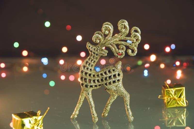 Goldenes Ren und kleine Geschenke auf Weihnachtshintergrund mit bokeh Lichtern lizenzfreie stockbilder