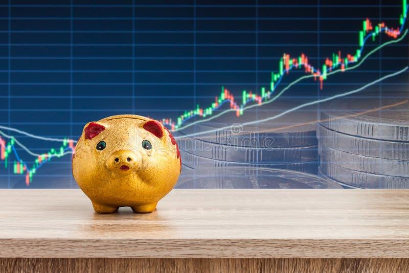 Goldenes Sparschwein auf Holztisch mit Aktienkurvehintergrund, stockfoto