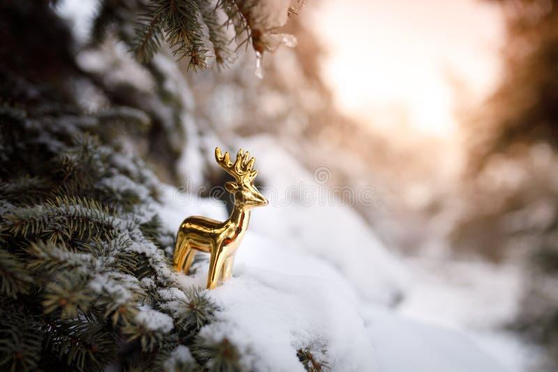 Goldenes Spielzeugrotwild steht auf einer Niederlassung eines Weihnachtsbaums im Schnee im Winter als Symbol des Neujahrsfeiertag stockfoto