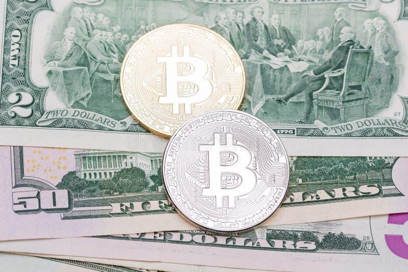 Goldenes und silbernes bitcoin auf US-Banknoten lizenzfreie stockfotografie