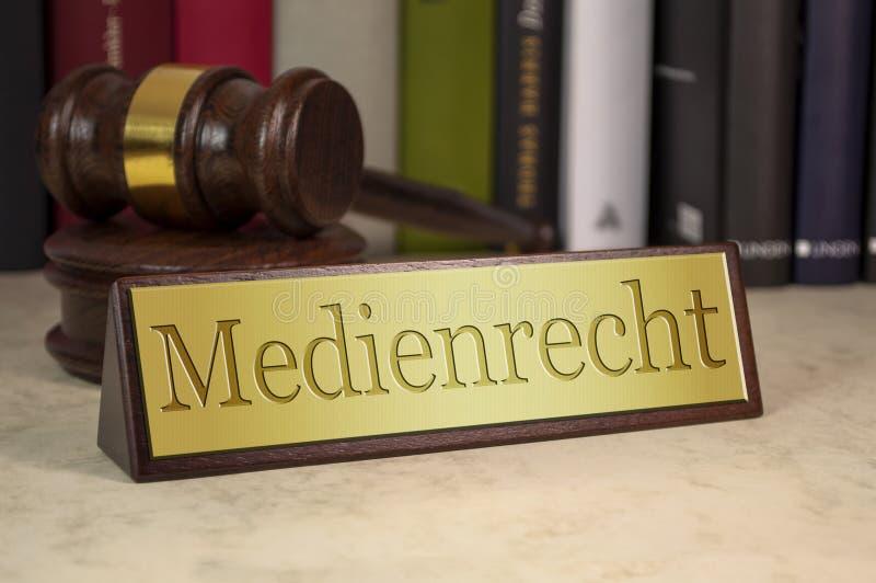 Goldenes Zeichen mit Hammer auf einem Schreibtisch mit dem deutschen Wort für Medien-Gesetz - Medienrecht lizenzfreie stockfotos