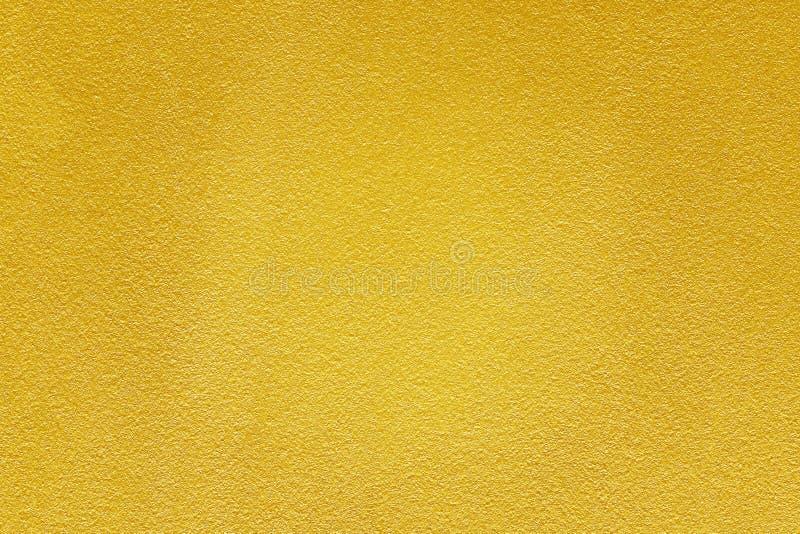 Goldfarbe auf rauem Zementwand-Beschaffenheitshintergrund stockbild