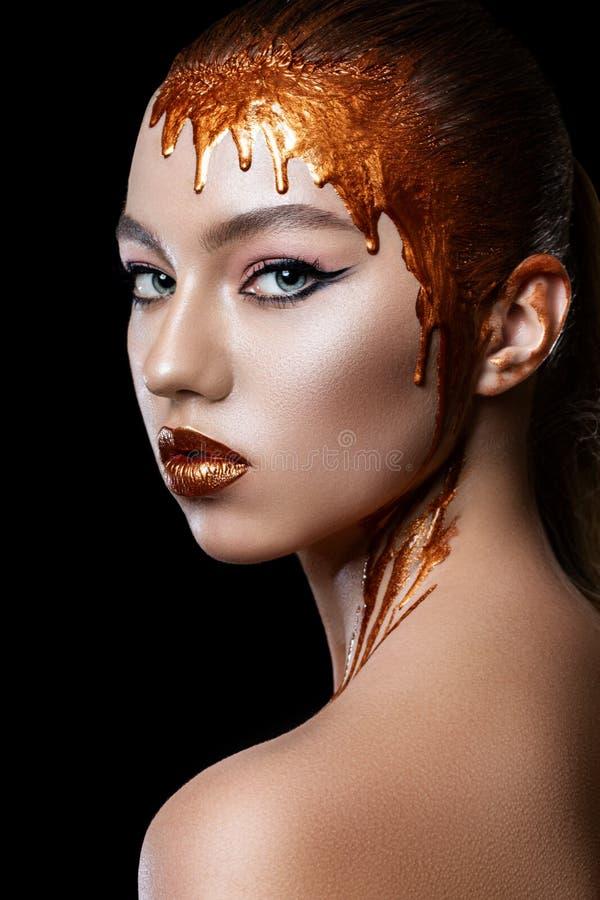 Goldfarben fließen unten von den Lippen, vom Gesicht und vom Hals eines schönen vorbildlichen Mädchens, kreatives abstraktes Make stockfotografie