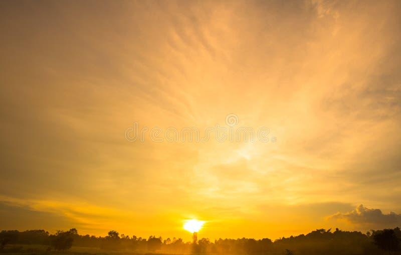 Goldfarbsonnenuntergang-Himmelhintergrund mit Sonne stockfoto