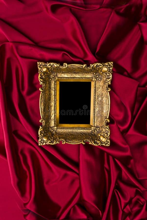 Goldfeld auf rotem Satin stockfotos