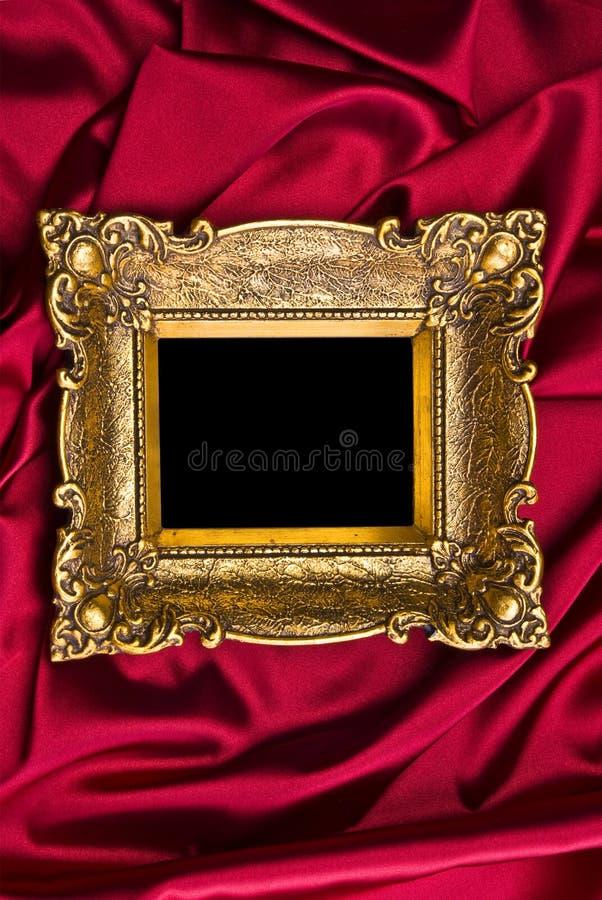 Goldfeld auf rotem Satin stockfotografie