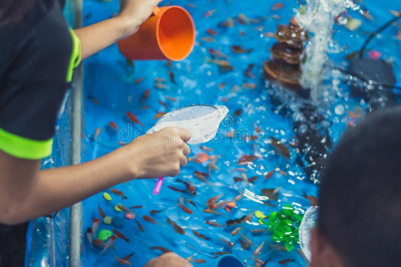 Goldfish scooping with kids on Annual festival. Goldfish scooping with kids in evening on Annual festival stock photo