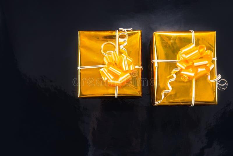 Goldfolienumwickelte Weihnachtsgeschenke auf Schwarzem lizenzfreies stockbild