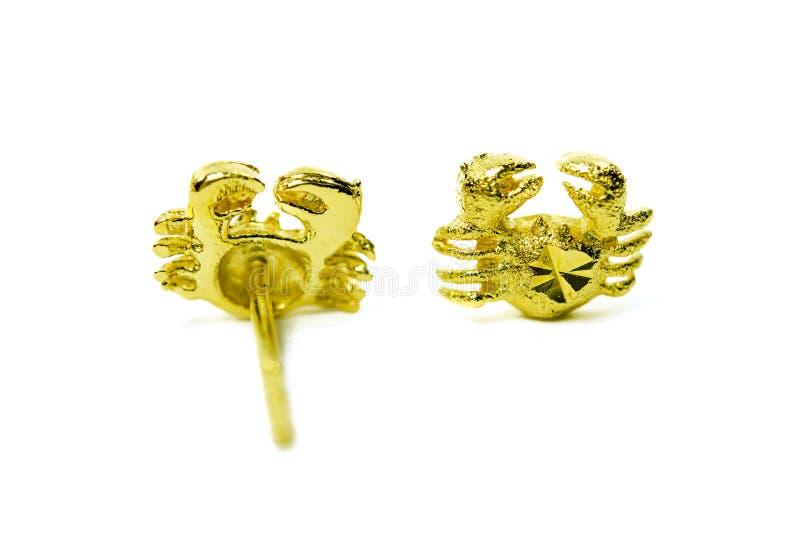 Goldhängender Miniatur-Ohrringschmuck in der Krabbenform lokalisiert auf whi lizenzfreie stockfotos