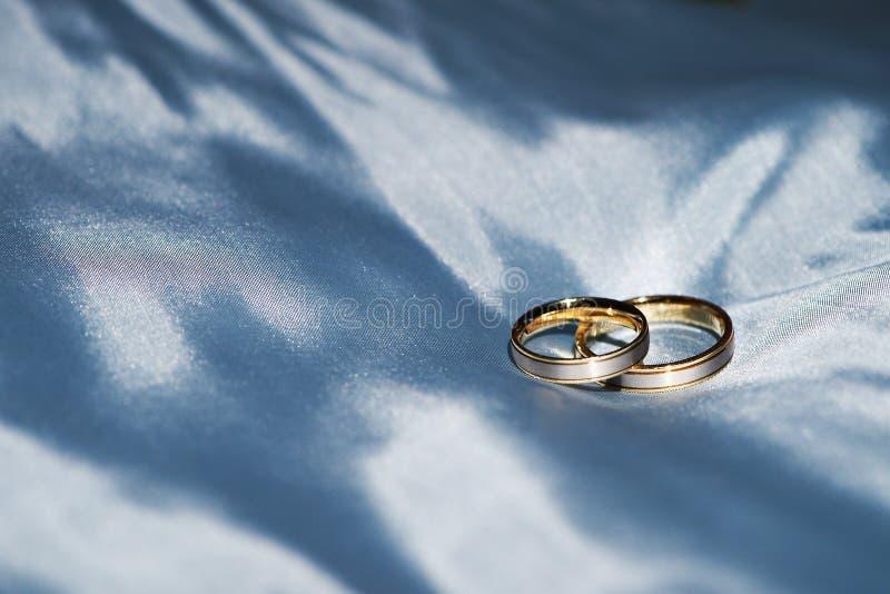 Goldhochzeitsring auf einer blauen Seide stockbild