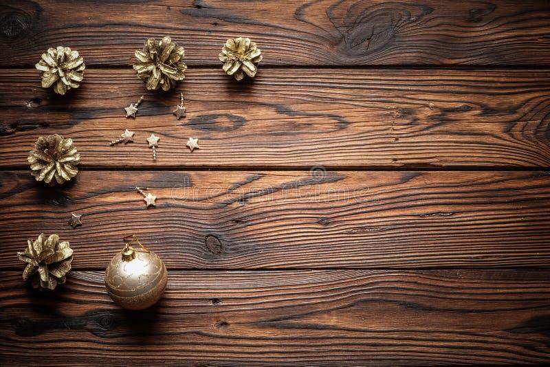Goldkiefer, Metallsterne und glitzernder Weihnachtsball auf der dunkelbraunen Holzoberfläche stockfotografie