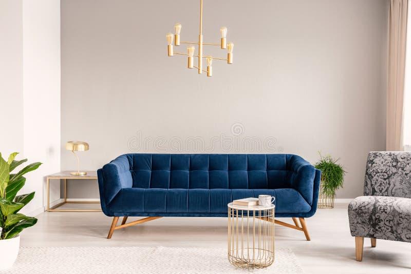 Goldlampe, die über Königsblausofa im wirklichen Foto des hellgrauen Wohnzimmerinnenraums mit leerer Wand hängt lizenzfreie stockbilder