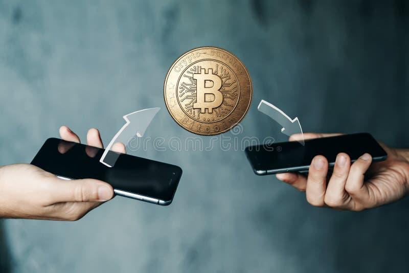 Goldmünze Bitcoin-Zahlung von Telefon zu Telefon, Hände und Fernsehnahaufnahme Das Konzept der Schlüsselwährung Blockchain-Techno lizenzfreies stockbild
