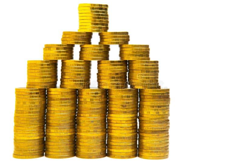 Goldmünzestapelhaus- oder -pyramidenform lokalisiert auf Weiß lizenzfreies stockfoto