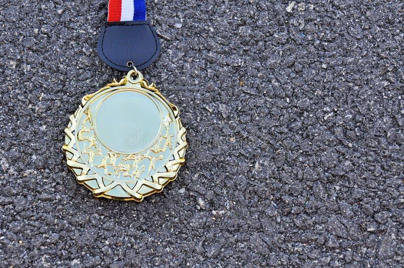Goldmedaille auf Asphaltstraße mit Kopienraumbereich lizenzfreie stockfotografie