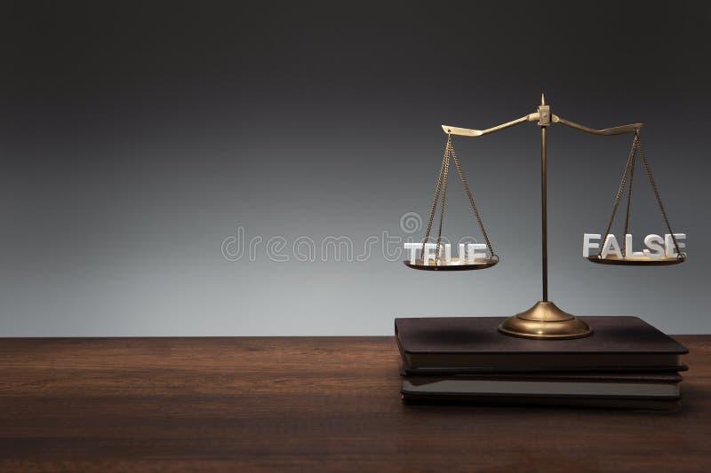 Goldmessingbalancen-Skalaplatz auf Notizb?chern und h?lzernem Schreibtisch- und Grauemhintergrund mit h?lzerner Text WAHREM FALSC lizenzfreie stockfotos