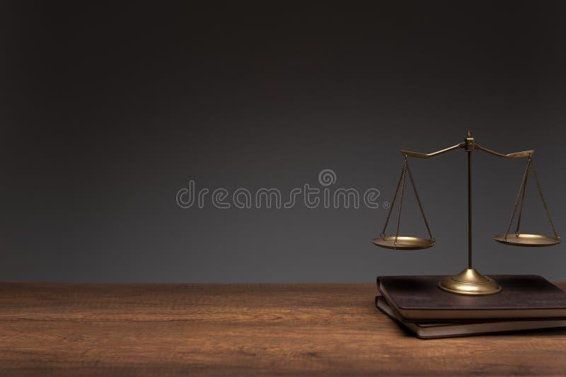 Goldmessingbalancenskala gesetzt auf die Weinlesebuch- und hölzernetabelle mit grauem Hintergrund stockfotografie