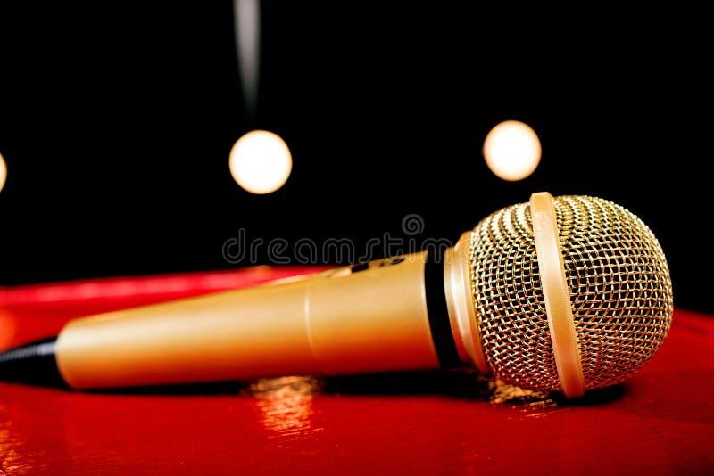 Goldmikrofon auf dunklem Hintergrund mit vielen Lichtern lizenzfreie stockfotografie