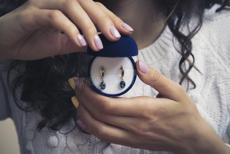 Goldohrringe mit blauem Topas in den Händen der Frauen stockfoto