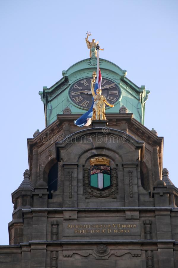 Goldplated art with clock and crest of the city of Rotterdam on the city hall at the Coolsingel stock photos