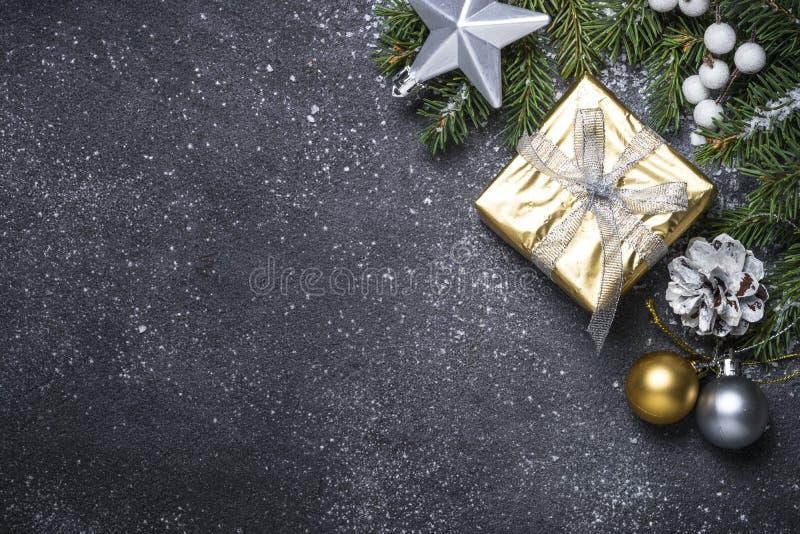 Goldpräsentkarton und -dekorationen auf schwarzem Steinhintergrund stockbilder