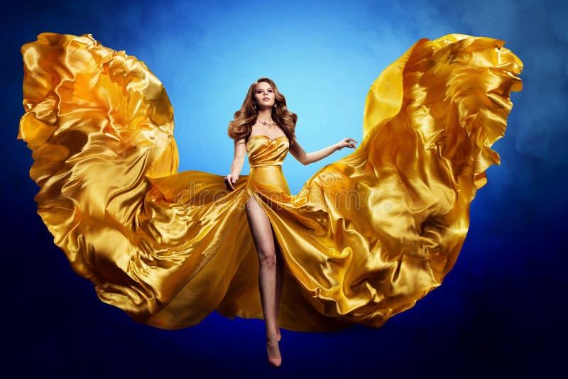 Goldseidenkleid für Frauen, Modemodellschmuck, Wellenflatterkleid lizenzfreie stockbilder