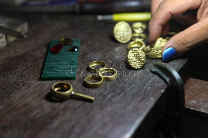 Goldsmith checking ring after casting. stock photos
