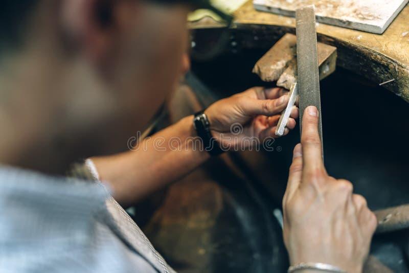 Goldsmith polishing metal bar royalty free stock photography