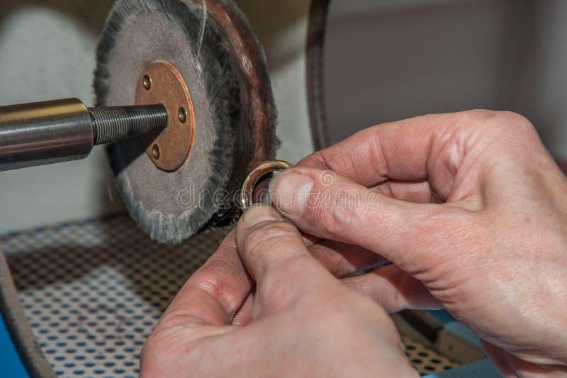 Goldsmith polishing a ring 1 royalty free stock photography