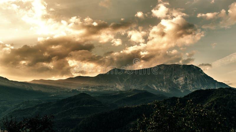 Goldsonnenuntergang über Berg Sonnenstrahlen, die durch die Wolken filtern lizenzfreie stockbilder