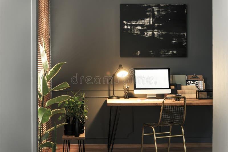 Goldstuhl, der den hölzernen Schreibtisch mit Lampe, Notizbücher bereitsteht und stockfotos