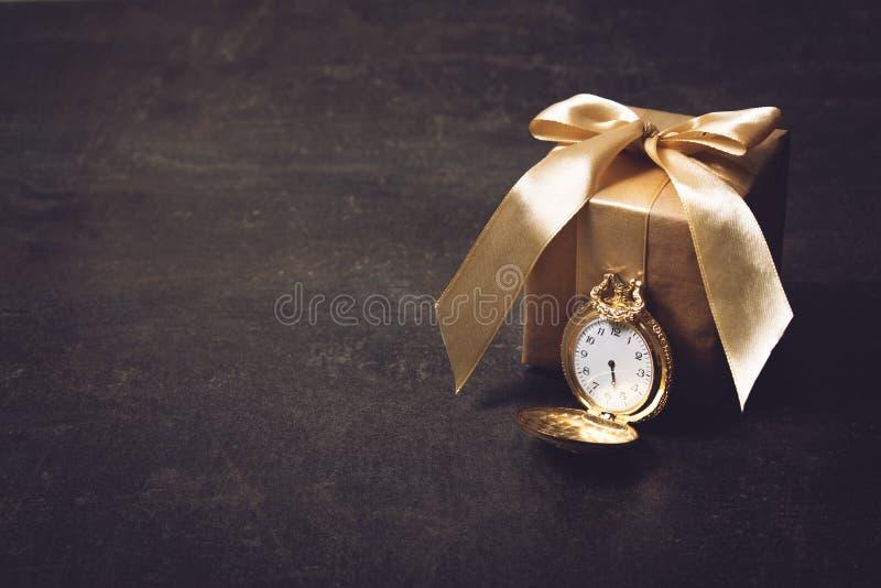 Goldtaschenuhr und Papiergeschenk mit Band auf dunklem Hintergrund Heirat, elegant, Liebe, Romanze, Valentinsgrußtageskonzept stockfotografie