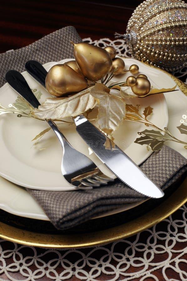 Goldthema Weihnachtsessengedeck. Schließen Sie oben auf Tischbesteck und Platten stockfotografie
