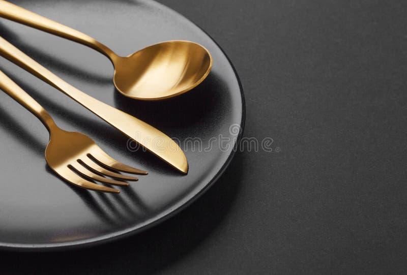 Goldtischbesteck eingestellt auf schwarzen Hintergrund lizenzfreies stockbild