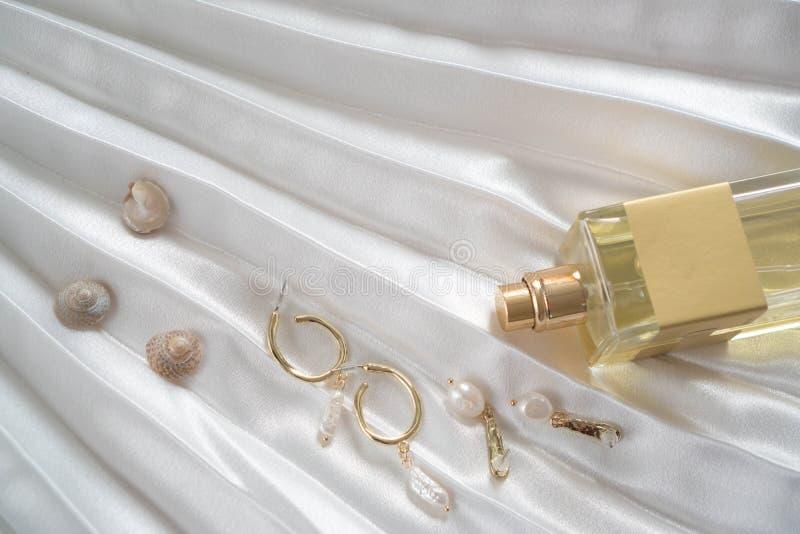 Goldweibliche Ohrringe mit Perlen, Flasche Parfüm auf einem schönen weißen drapierten Satingewebe mit Oberteilen Elemente der Fra stockbilder