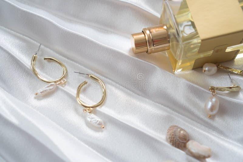 Goldweibliche Ohrringe mit Perlen, Flasche Parfüm auf einem schönen weißen drapierten Satingewebe mit Oberteilen Elemente der Fra lizenzfreies stockfoto