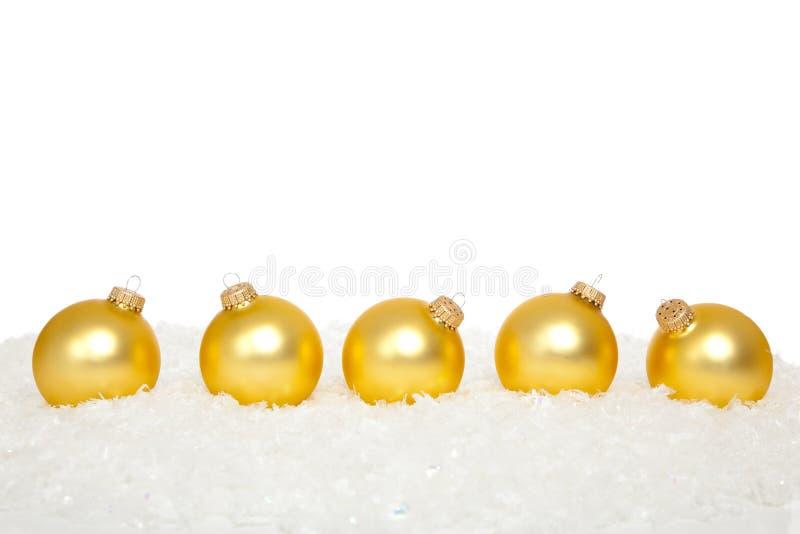 Goldweihnachtsverzierungen im Schnee stockbild