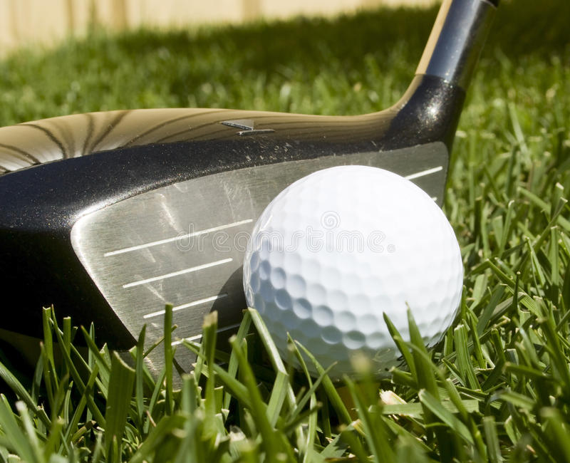 Golf. Ball on a tee with a driver stock images